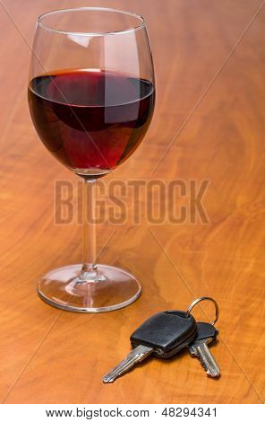 Red wine glass with car keys on a wooden background