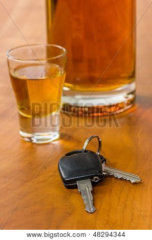 Shot glass with car keys on a wooden background
