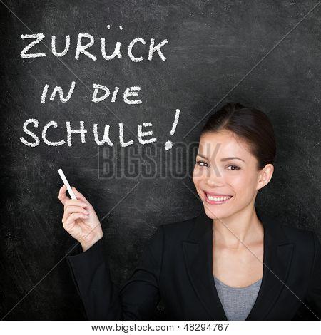 Zuruck in die Schule - German teacher woman. Back to School written in German on blackboard by female on chalkboard. Woman professor teaching German language at college, high school or primary school.