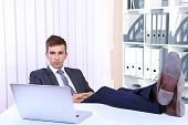 pic of table manners  - Businessman resting at his office with his shoes on table - JPG