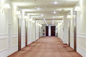 picture of lamp shade  - Spacious light hallway with many doors leading into hotel rooms - JPG