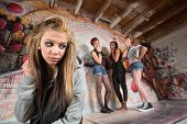 stock photo of peer-pressure  - Unhappy blond girl near cruel group of teens - JPG