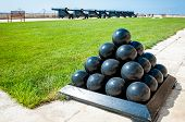 stock photo of cannonball  - Old cannonballs stacked in pyramid in front of blured cannons on Valletta Castle Malta - JPG