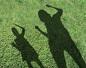 image of bullying  - Bullying kids and school bully concept with the shadows of two children with one smaller child being threatened and abused by the older kid on green grass as a symbol of school safety from bullies - JPG
