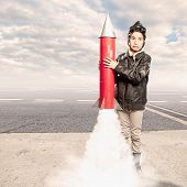 stock photo of turbines  - little aviator holding a rocket at the airport - JPG