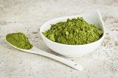picture of moringa oleifera  - moringa leaf powder in a small bowl with a spoon against a ceramic tile background - JPG
