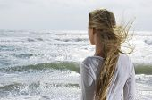 stock photo of windswept  - Rear view of a young blond woman looking at the ocean - JPG
