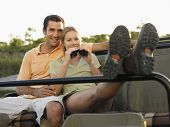 foto of  jeep  - Young couple sitting in jeep with woman holding binoculars - JPG