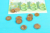 Euro banknotes and euro cents on blue background