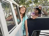 stock photo of campervan  - Portrait of happy young woman with boyfriend leaning out of campervan during road trip - JPG