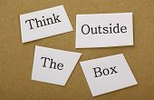 stock photo of thinking outside box  - Think Outside the box in cut out text on a background of brown cardboard - JPG