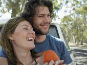 stock photo of campervan  - Loving young couple embracing in front of campervan during road trip - JPG