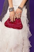 closeup of bride wearing ruffles dress and red luxury bag with fashion bangles and large diamond rin