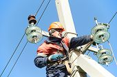stock photo of pole  - Electrician lineman repairman worker at climbing work on electric post power pole - JPG
