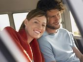 stock photo of campervan  - Portrait of smiling young woman with boyfriend in campervan - JPG