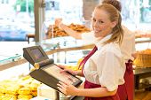 stock photo of cash  - Cashier in a bakery posing with cash register - JPG