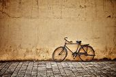 stock photo of bicycle gear  - Old rusty vintage bicycle near the concrete wall - JPG