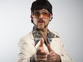 stock photo of cheeky  - Portrait of a retro man in a 1970s leisure suit and sunglasses pointing to the camera - JPG