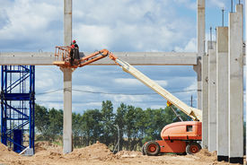 foto of mortar-joint  - builder worker putting cement mortar on concrete pole joint at construction site using lifting boom machinery - JPG