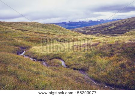 Small Stream Of Water Flowing Through Hillside