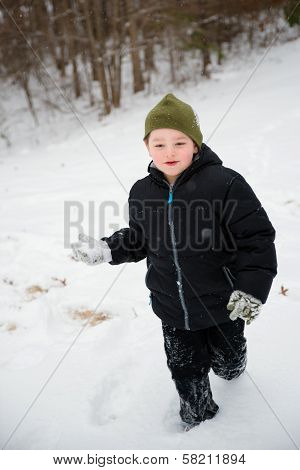 Child playing in snow running with snowball