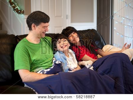 Family With Disabled Boy Relaxing Together On Leather Couch
