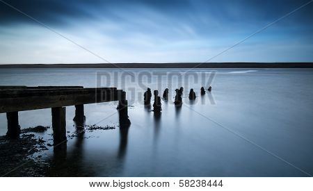 Long Exposure Landscape Of Old Derelict Jetty Extending Into Lake