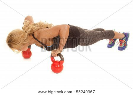 Mature Woman Doing Pushup On Kettle Bells