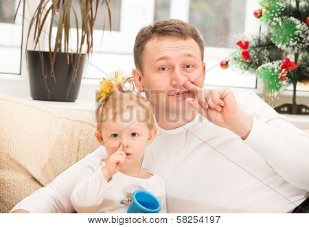 Happy Father And Child Girl Hugging And Picking His Nose