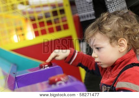 Boy Playing On Game Machine