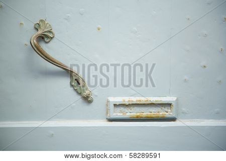 Light blue wooden door with artistic handle
