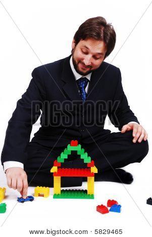 Jonge Mane dragen pak Is het maken van een huis met kubussen speelgoed