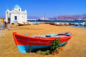 stock photo of old boat  - Mykonos harbor with old boat and blue dome church - JPG