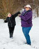 image of snowball-fight  - Mother and son playing in snow by having snowball fight - JPG