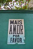 stock photo of por  - Mais amor por favor poster in a green wall - JPG