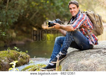 handsome young photographer resting in mountain valley
