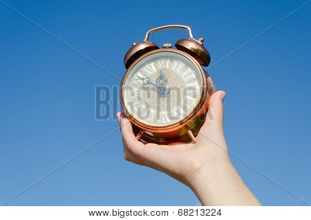 Clock Roman Numeral In Hand On Blue Sky Background