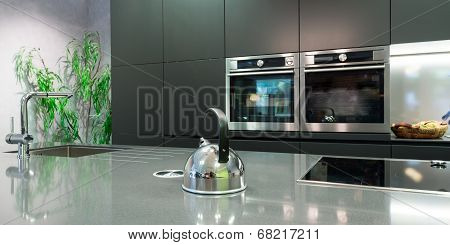 detail over work plate of modern kitchen with teapot and baking oven