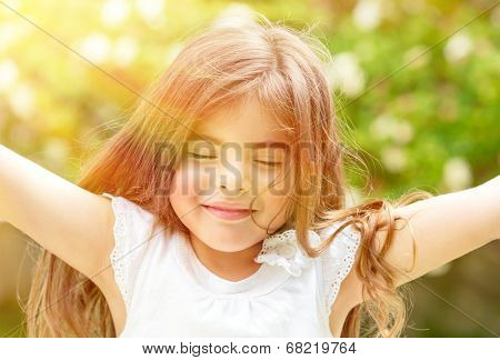 Portrait of attractive little Arabic girl with closed eyes enjoying sunny day, having fun outdoors, pleasure and happiness concept