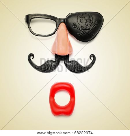 a funny face formed with fake mouth, nose and glasses with mustache and pirate patch on a beige background, with a retro effect