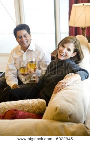 Mature couple drinking wine together on couch in living room
