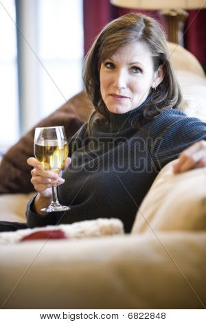 Mature woman relaxing on sofa drinking wine