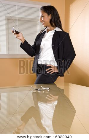 Young African-American woman in office boardroom texting on mobile phone