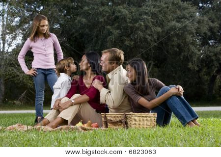 Interracial family of five having picnic in park