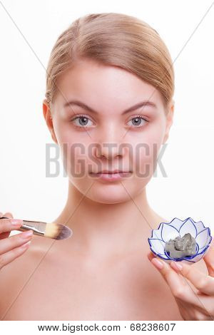 Woman Applying Clay Mask On Face
