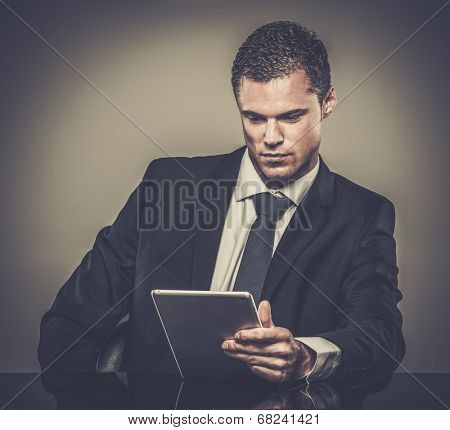 Well-dressed man in black suit with tablet pc