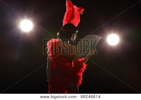 Burlesque dancer with red plumage and short dress, black background