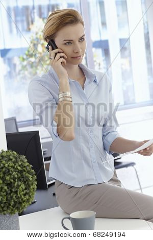Beautiful young businesswoman talking on mobilephone, sitting on top of desk, holding paper.