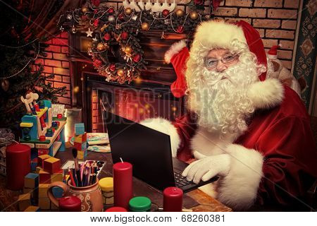 Santa Claus sitting at the table with a laptop at his home. Christmas time.