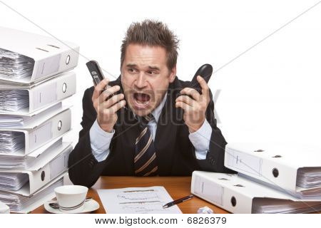 Stressed Business Man With Telephones Screaming Frustrated Between Folder Stacks In Office